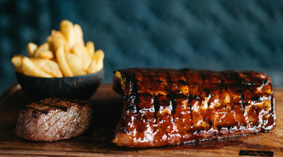 wooden board of ribs eye fillet steak and chips
