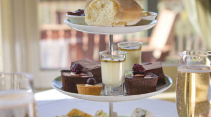 three tier high tea stand with sandwiches dessert slices and scones