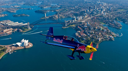 red bull aerobatic plane flying above sydney harbour
