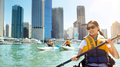 group kayaking brisbane river with city skyline views