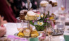 The tea salon high tea stand with cakes scones and sparkling champagne