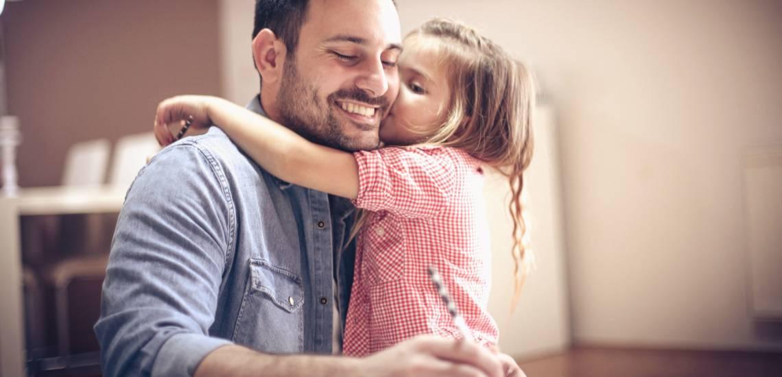 Na imagem, filha ainda criança abraça e beija seu pai no dia dos pais