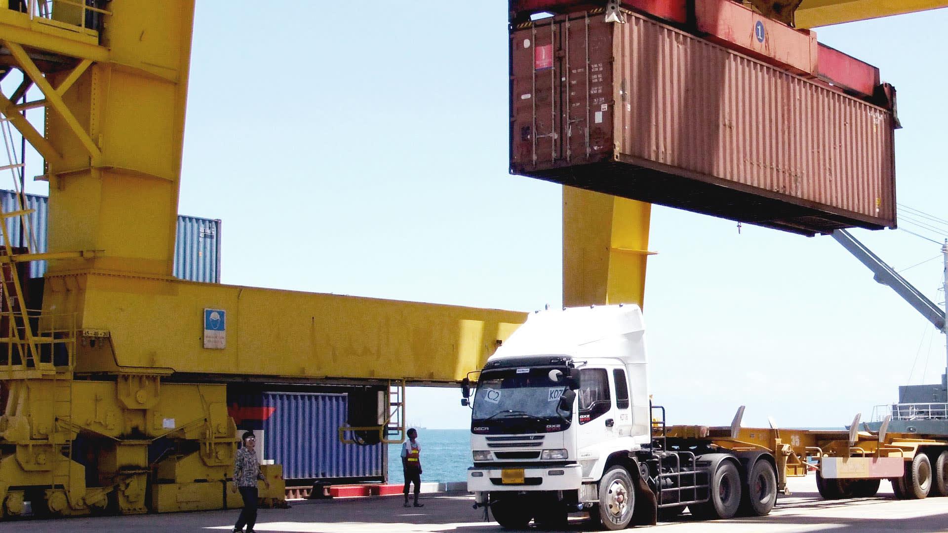 Na imagem, carga sendo transportada por caminhão.