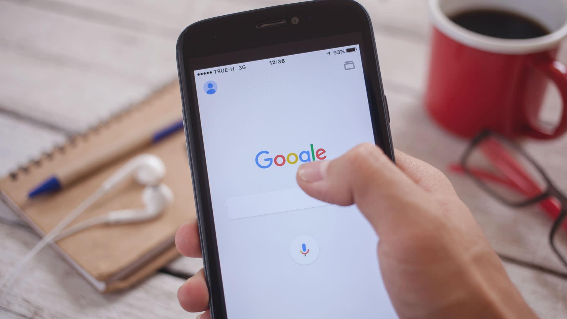 Na imagem, vemos uma mão segurando um celular  com a tela inicial do Google