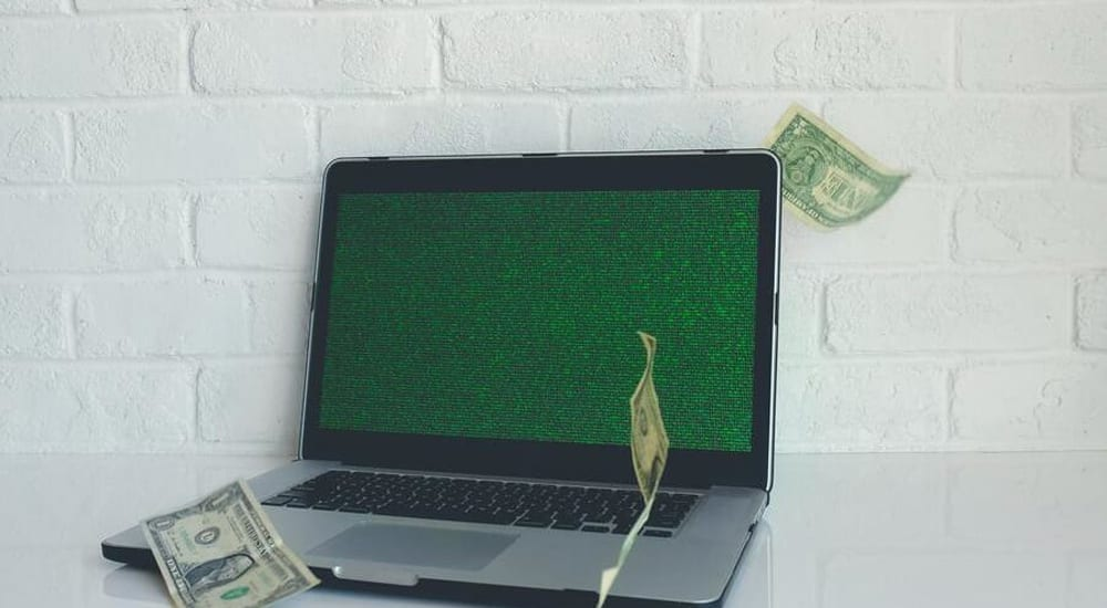 Dollar bills falling around an open laptop on a table