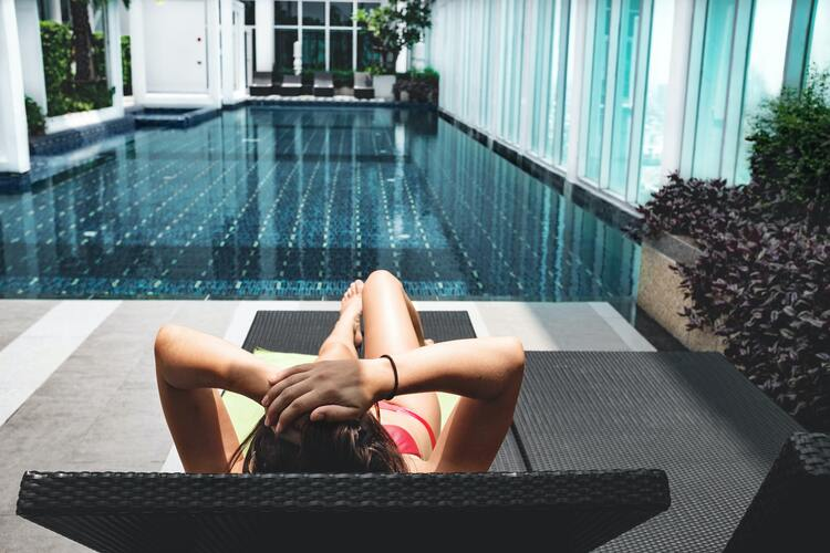 Girl laying on lounge chair by a swimming pool