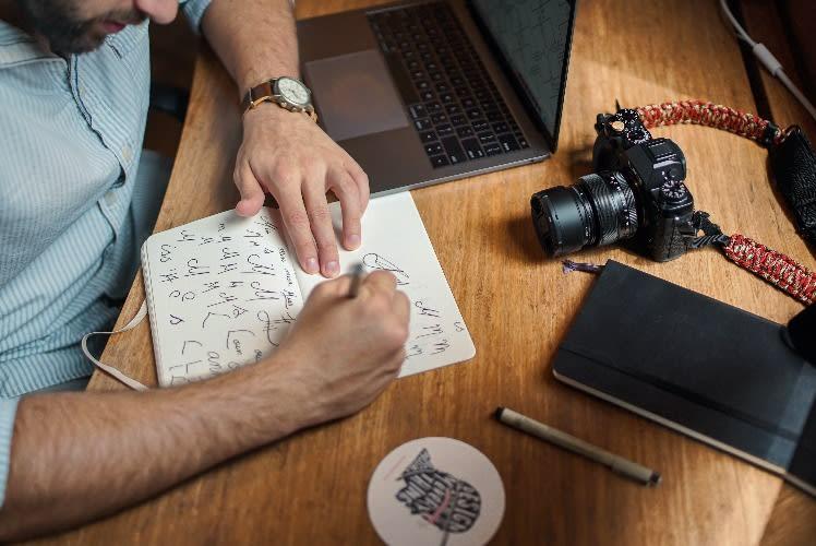 Man sketching logo designs on paper