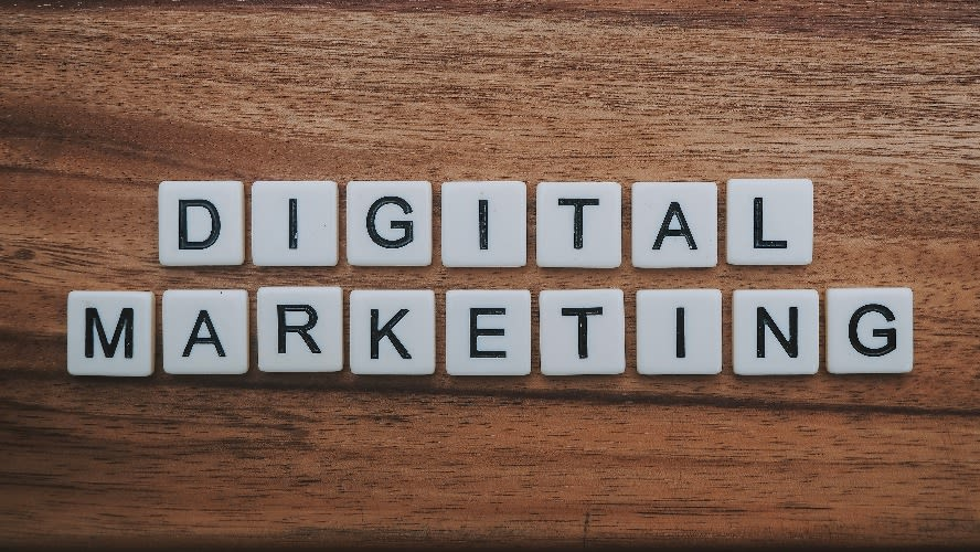 """scrabble pieces on wooden table spelling out """"digital marketing"""""""