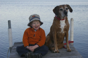 Kid and dog on dock at Cozy Bay Resort.