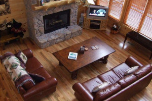 Living room of Crockett Mtn Lodge, situated around the gas log fireplace and adjoining the kitchen and dining room area.