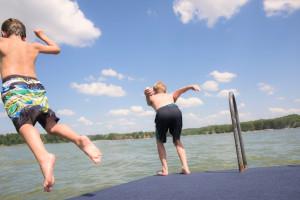 Jumping in lake at Delton Oaks Resort.