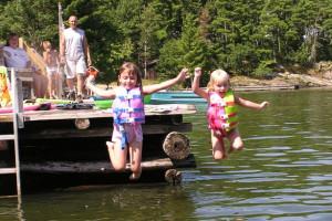 Kids jumping in lake at Arrowhead Lodge & Resort.