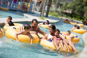 Family in lazy river at Sands Resorts.