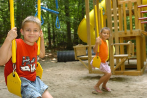 Kids playing on playground at Hemlock Campground & Cottages.