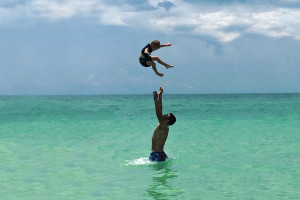 Family swimming at beach at beachrentals.mobi. LLC.