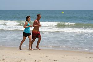 Couple running on the beach near Sea Hawk Motel.