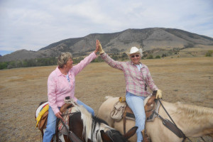 Couple horseback riding at Vee Bar Guest Ranch.