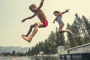 Kids jumping into lake at Westward Shores Camping Resort.