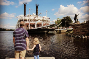 Family watching river boat at Eagles on the River and Anderson House Hotel.