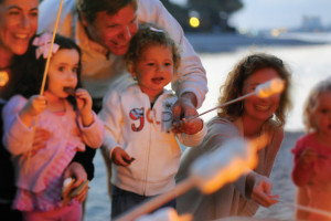 Family roasting marshmallows at Bellmere Winds Resorts.