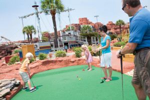 Family playing mini golf at The Strand Resort Myrtle Beach.