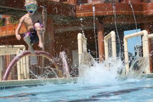 Kid jumping in pool at Landmark Resort.