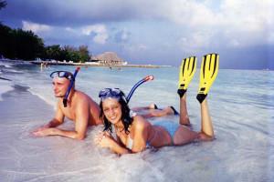 Couple snorkeling on beach at Giravaru Tourist Resort.