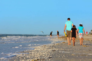 Family walking on beach at The Inns of Sanibel.