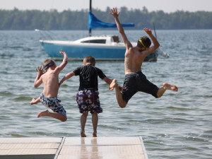 Jumping in the lake at Visit Up North Vacation Rentals.