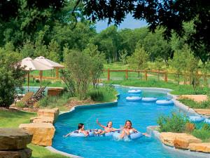 Family swimiming in river pool at Hyatt Regency Lost Pines Resort and Spa.
