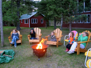Family by the fire pit at Two Inlets Resort.
