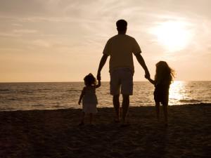 Family on beach at Sanctuary Realty At Sandbridge.