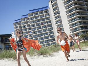 Family running on beach at Carolina Winds.