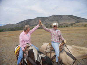 Couple horseback riding at Vee Bar Guest Ranch.