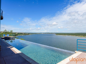 Rental pool with lake view at Utopian Austin Vacation Rentals.
