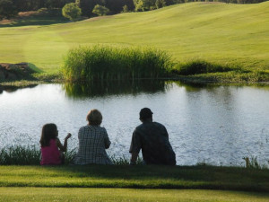 Family sitting by pond at Greenhorn Creek Resort.
