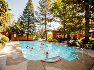 Many guests enjoy the outdoor heated pool at Half Moon Trail Resort. It is surrounded by gardens and is steps away from a hand dipped malt in the classic lodge.