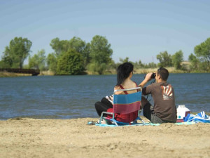 Couple sitting on shore at Lake Oroville.