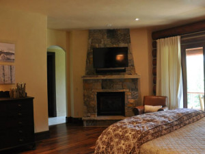 Vacation rental bedroom with fireplace at SilverStar Luxury Properties.