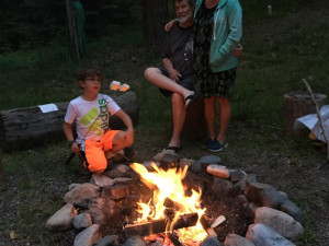 Family roasting marshmallows at Bear Paw Lodge.