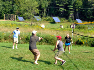 Families enjoy a pick-up game of volleyball at Common Ground Center.