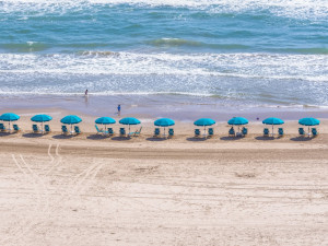 Beach with umbrellas at Padre Getaways.