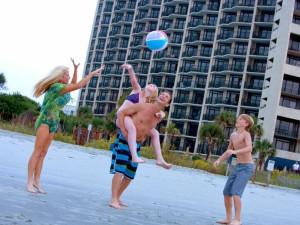 Family playing on beach at Ocean Reef Resort.