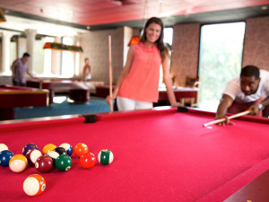Playing a game of billiards at Poconos Palace from Cove Haven Entertainment Resorts.