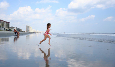 Kid on beach at MyrtleBeachVacationRentals.com.