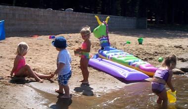 Kids playing on the beach at Black Pine Beach Resort.