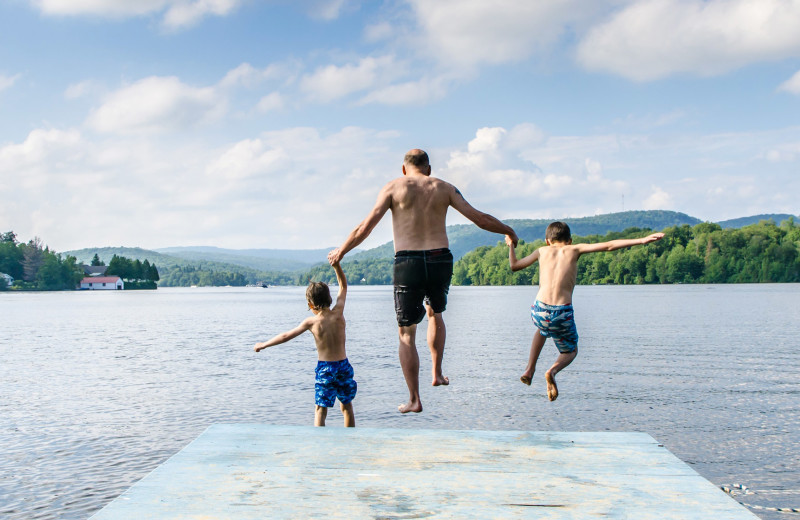 Family jumping in lake at Great Blue Resorts.