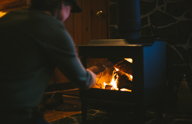 Stoking the wood stove in the cabin at Falcon Beach Ranch