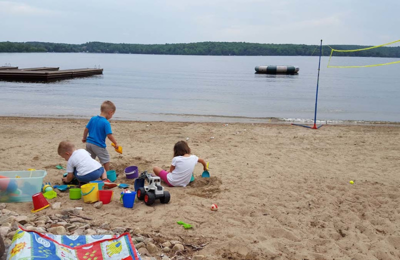 Family on beach at All-Season Cottage Rentals.