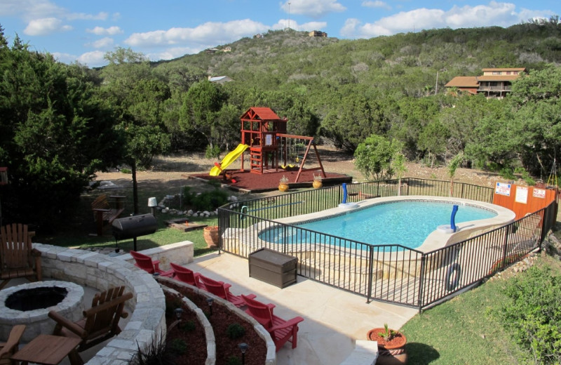 Rental pool, patio, and playground at Frio River Vacation Rentals.